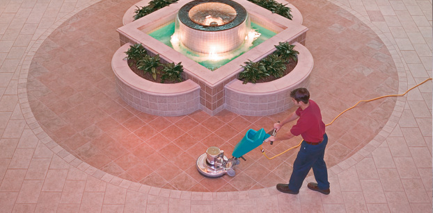 Man polishing tile around fountain