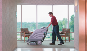 Man cleaning carpet in an office using a wet vac